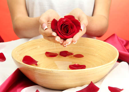 woman hands with wooden bowl of water with petals, on red background Stock Photo - 15897826