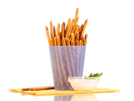 Tasty crispy sticks in purple plastic cup isolated on white photo