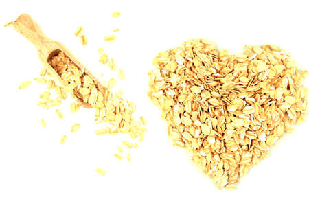 Heart shape made from oat flakes with wooden scoop isolated on white Stock Photo - 15897816