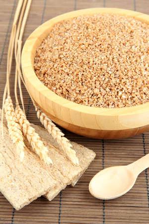 Wooden bowl full of wheat bran photo