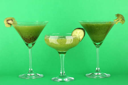 Three kinds of green juice in coctail glasses on color background photo