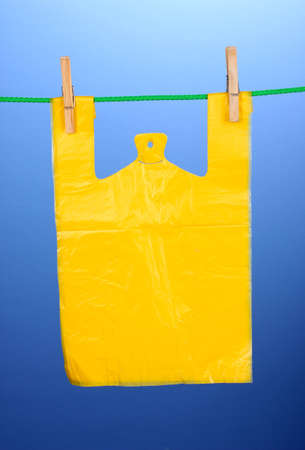 Cellophane bag hanging on rope on blue background photo