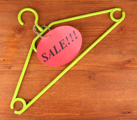coat hanger with sale tag on wooden background photo