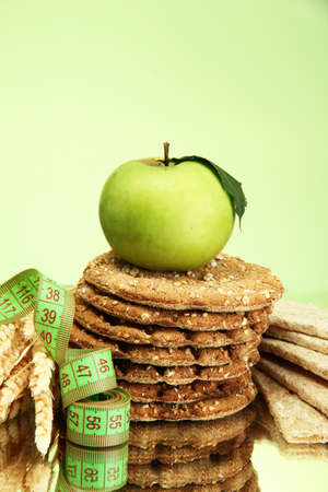 tasty crispbread, apple, measuring tape and ears, on green background Stock Photo - 15924482