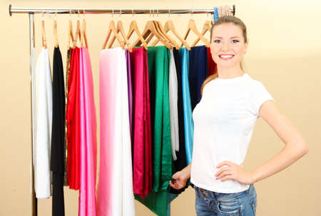 clothing rack: beautiful young woman near rack with hangers Stock Photo