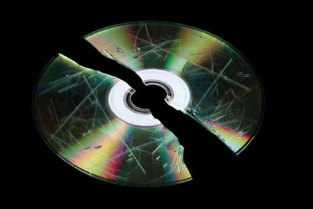 gigabyte: Defective and broken disk with information isolated on black Stock Photo
