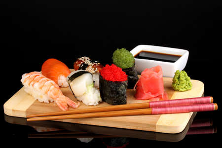 delicious sushi served on wooden board isolated on black photo