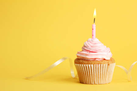 1 object: tasty birthday cupcake with candle, on yellow background