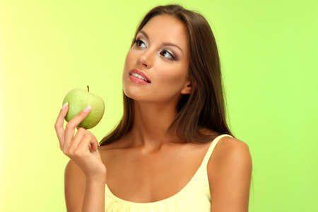 beautiful young woman with green apple, on green background photo