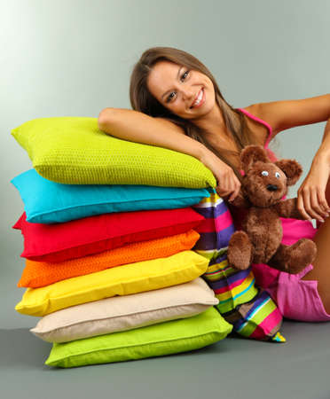 beautiful young girl and fluffy bear with pillows on grey background Stock Photo - 16346509