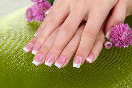 cosmetic lacquer: Woman hands with french manicure and flowers on green background Stock Photo