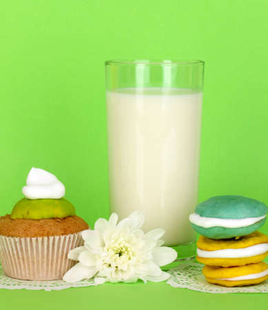 pasteurized: Glass of fresh new milk with cakes on green background