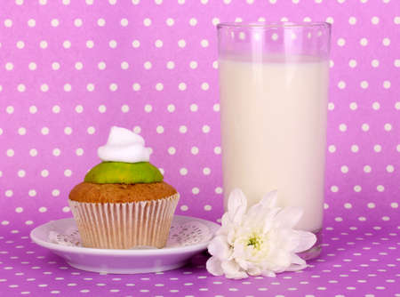 pasteurized: Glass of fresh new milk with cake on purple polka dot background