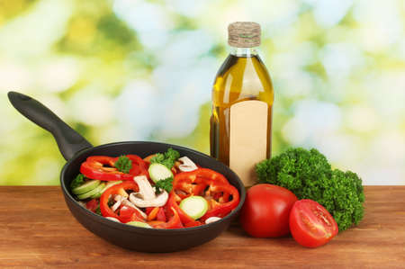 frying pan with vegetables on green background Stock Photo