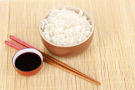 Bowl of rice and chopsticks on bamboo mat photo