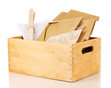 Wooden crate with papers and letters isolated on white photo