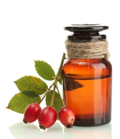 medicina natural: botella de la medicina con las rosas cadera, aislada en blanco