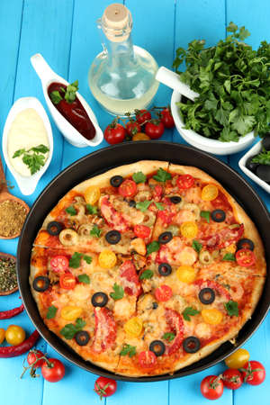 colorful composition of delicious pizza, vegetables and spices on blue wooden background close-up Stock Photo - 15964293