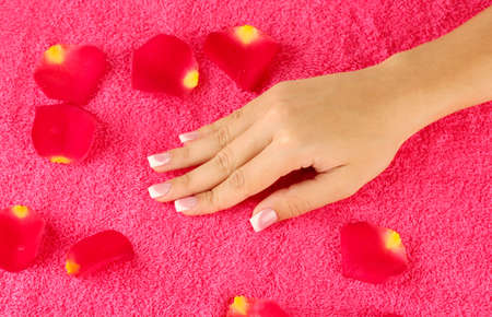 womans hand on bright pink terry towel, close-up photo