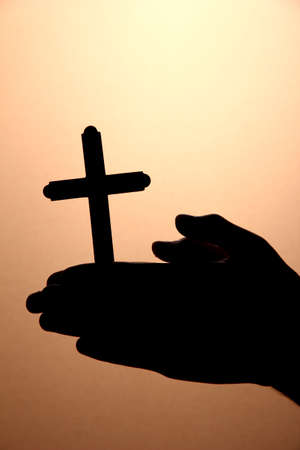 mano de dios: las manos del hombre con crucifijo, en el fondo marr�n Foto de archivo