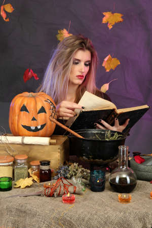 Halloween witch preparing poison soup in her cauldron on color background photo