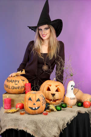 Halloween witch with pumpkins on color background photo