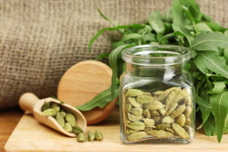 Jar of green cardamom with rocket on canvas background close-up photo