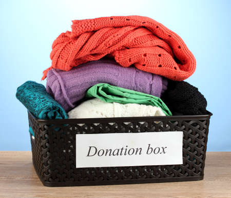 Donation box with clothing on blue background close-up Stock Photo - 15964828