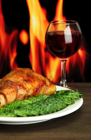 Roast chicken with french fries and cucumbers, glass of wine on wooden table  on fire background photo