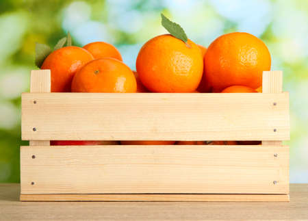 wooden crate: Ripe tasty tangerines with leaves in wooden box on table on green background