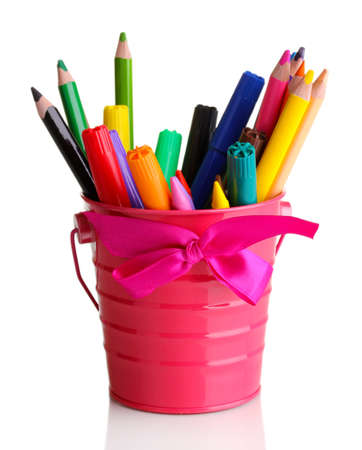 Colorful pencils and felt-tip pens in pink pail isolated on white photo