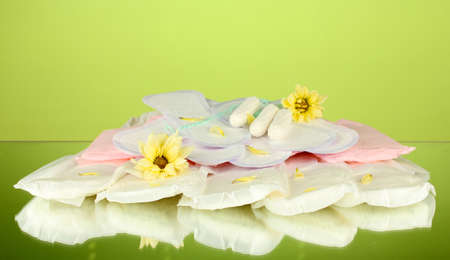 various types of sanitary pads and tampons on green background close-up Stock Photo - 15964692