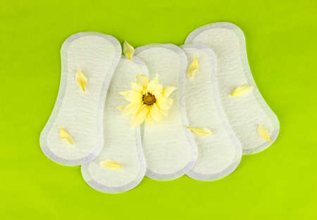 daily panty liners and yellow flower on green background close-up photo