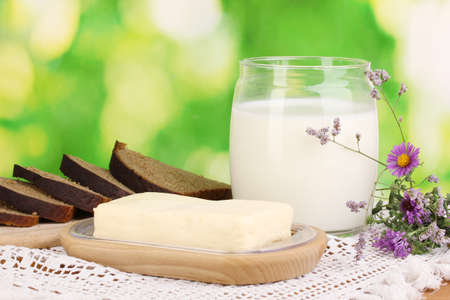 Butter on wooden holder surrounded by bread and milk on natural background Stock Photo - 15964840