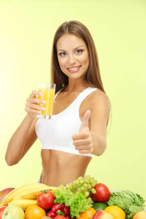 beautiful young woman with fruits and vegetables and glass of juice, on green background photo