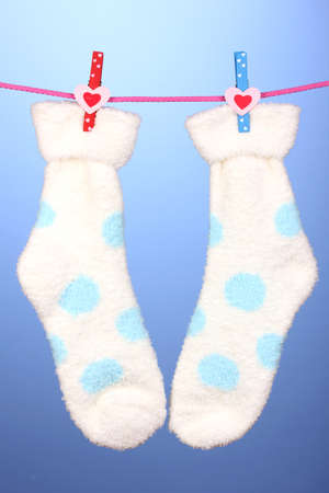 Pair of socks with polka dots hanging to dry over blue background photo