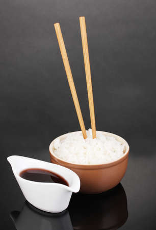 Bowl of rice and chopsticks on grey background photo