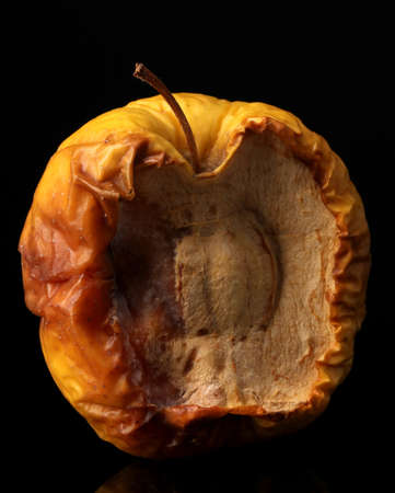 black mold: yellow moldy apple as concept of skin problems, isolated on black