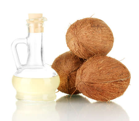 coco: decanter with coconut oil and coconuts isolated on white