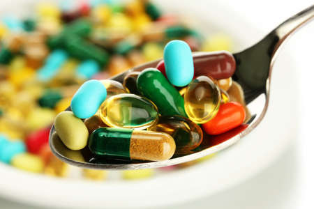 Colorful capsules and pills on plate with spoon, close up photo