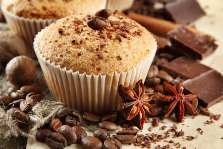 tasty muffin cakes with chocolate, spices and coffee seeds, on beige background photo