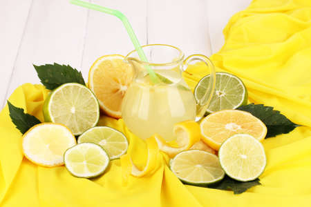 Citrus lemonade in glass pitcher of citrus around on yellow fabric on white wooden table close-up Stock Photo - 16037103
