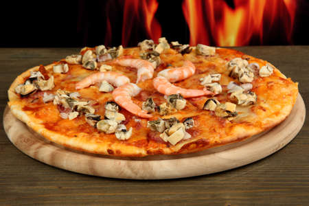 Delicious pizza with seafood on stand on flame background photo
