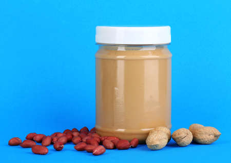 Delicious peanut butter in jar of peanut near on blue background photo