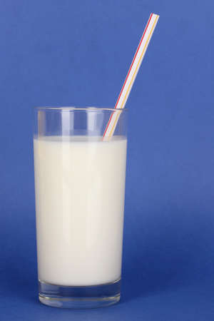 Glass of fresh new milk on blue background photo
