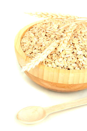Brown bowl full of oat flakes with spikelets and wooden spoon isolated on white Stock Photo - 16036449