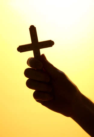 man hand with crucifix, on yellow background  photo