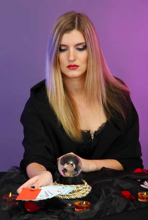 cartomancy: Witch - fortune teller on color background Stock Photo