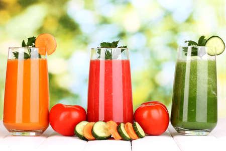 tomato juice: Fresh vegetable juices on wooden table, on green background