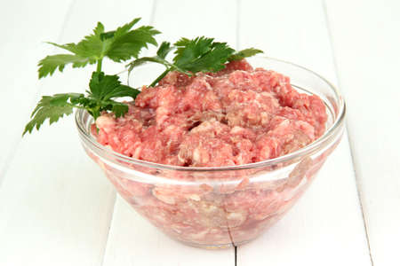 Bowl of raw ground meat on wooden table Stock Photo